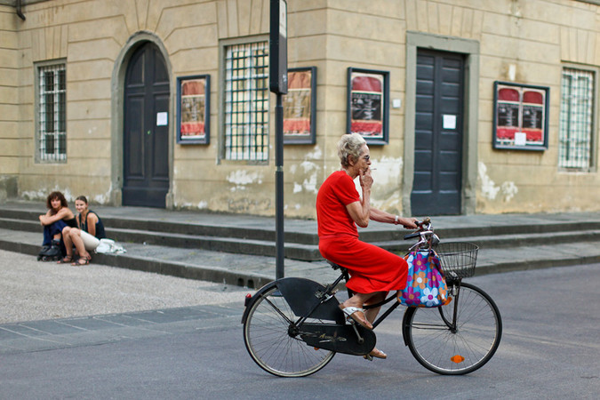 Lucca Italy pictures of a woman riding a bicycle and smoking
