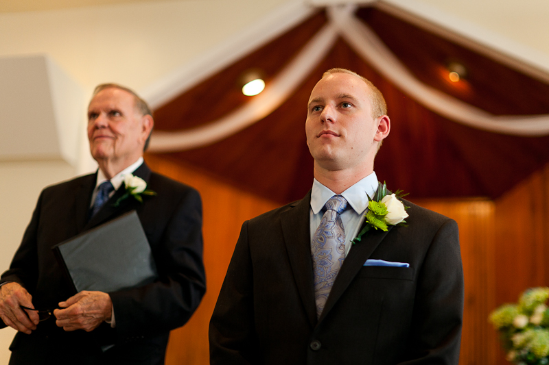 Groom watching bride walk down isle